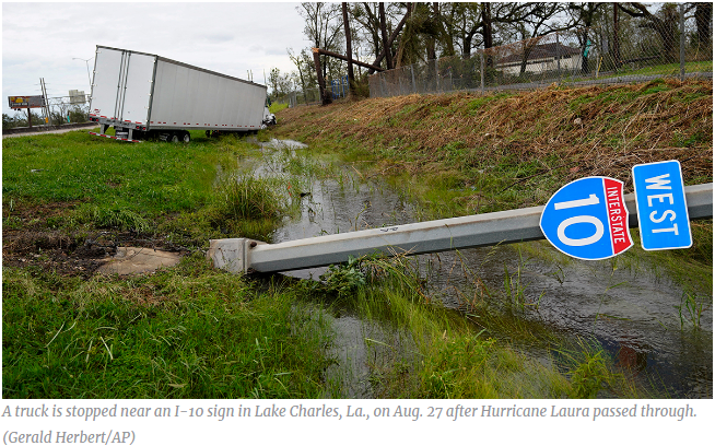 A truck is stopped near an I-10 sign in Lake Charles, La., on Aug. 27 after Hurricane Laura passed through.