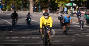 A man man riding a bicycle in a bright yellow jacket with other bicyclists and pedestrians in the background