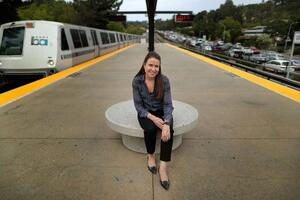 Susan Shaheen - in a navy patterned blouse and black pants - sits on a circular bench on the platform at the Orinda BART station in Orinda, California.