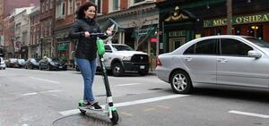 A woman in a black jacket rides a green Lime scooter on a street