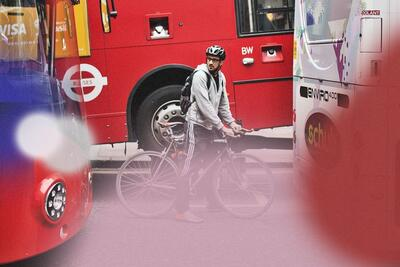 A man wearing a grey sweatshirt and black sweatpants rides a bicycle between three public transit buses