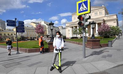 A man wearing a face mask rides a scooter near the Bolshoi Theatre in Moscow on May 15, during a strict lockdown in Russia to stop the spread of COVID-19.