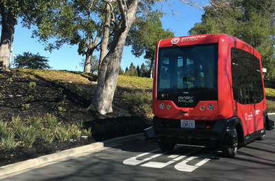 Image of a small, red boxy automated vehicle in front of some trees and shrubbery on a road